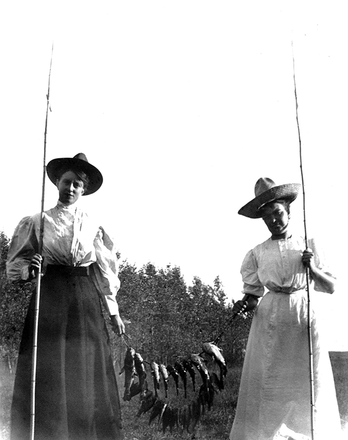 Women on Laramie Range with fishing poles and a string of catches