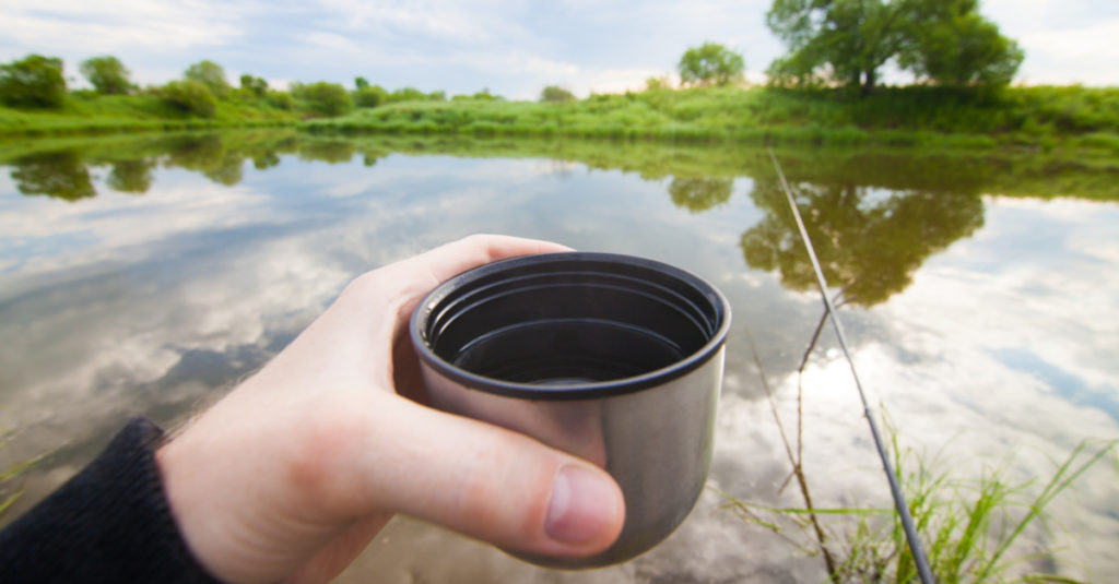 Fisherman on the bank with a cup of tea
