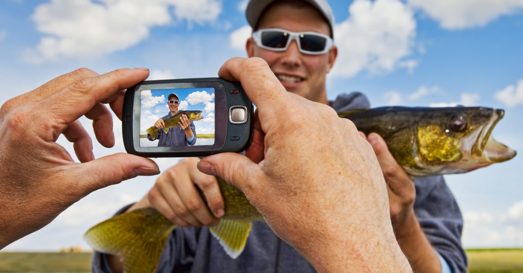 Fisherman getting his photo taken with his latest catch